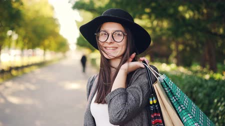 ветреный : Portrait of cheerful girl shopper posing with paper bags, looking at camera, smiling and laughing standing in the street in big city. Youth and shopping concept.
