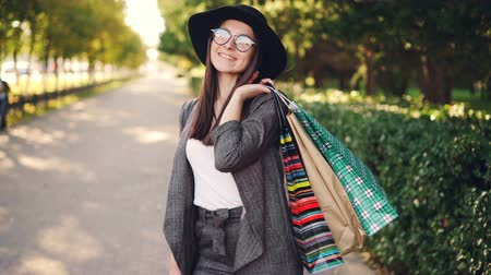 bolsa de compras : Portrait of pretty young woman holding paper bags standing outdoors in the city and looking at camera on sunny autumn day. Shopping, youth and street concept. Stock Footage