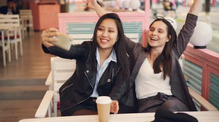 tomar : Carefree girls are taking selfie with take out drinks sitting in cafe together and using smartphone. Young women are posing, clinking glasses and showing hand gestures.