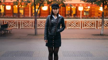 outsider : Zoom in time-lapse of pretty Asian girl looking at camera standing outdoors with hand in pocket wearing trendy leather jacket when people are moving around.
