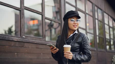 go away : Slow motion of attractive young woman walking in the street holding to-go drink and smartphone smiling and using gadget touching screen. Technology and emotions concept.