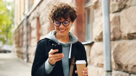 látszó el : Smiling young woman in glasses is using smartphone looking at screen while walking outdoors in city with to-go coffee. Youth lifestyle, street and technology concept.