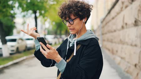 hablador : Young woman with curly hair and glasses is talking to friends online standing outdoors and using smartphone and earphones. Gadgets, internet and communication concept.