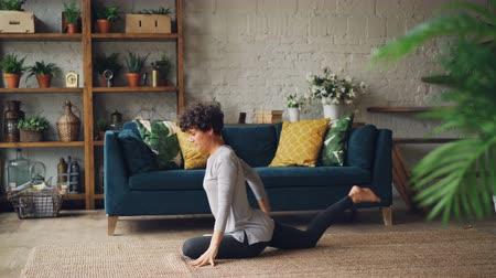 гибкий : Attractive young woman is stretching legs and arms sitting on floor during individual practice at home. Healthy lifestyle, interior and people concept.