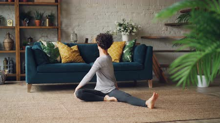 pozisyon : Flexible girl is bending forward in seated position and twisting her body enjoying yoga and activity sitting on floor in beautiful apartment. People and health concept. Stok Video