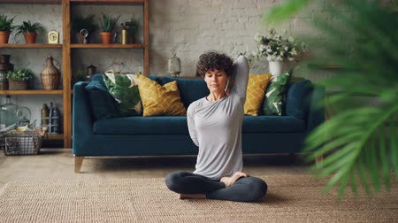 assentado : Pretty lady is stretching her arms behind her back sitting on floor in lotus position during personal training at home. Active lifestyle, people and health concept.