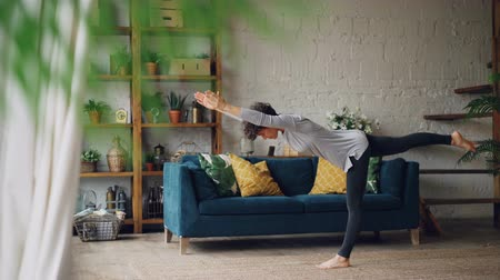 balanceamento : Active person is doing yoga at home practising balance exercises on one leg standing on floor alone. Beautiful loft style flat with furniture and plants is visible. Stock Footage