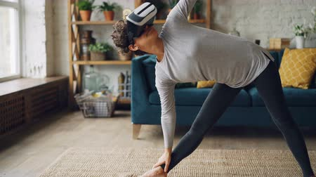 enjoyable : Attractive person is doing sequence of yoga asanas wearing artificial reality glasses during personal training at home. Sports, entertainment and interior concept.
