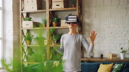 достигать : Happy girl is using virtual reality glasses at home standing in room moving hands and smiling having fun. Modern gadgets, entertainment and apartment concept. Стоковые видеозаписи