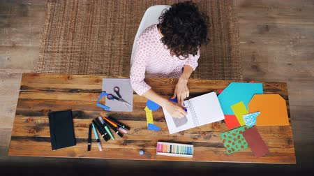 designing : Top view of busy female designer sticking paper figure in notebook using glue-stick working at home alone. Creativity, design and modern art concept. Stock Footage