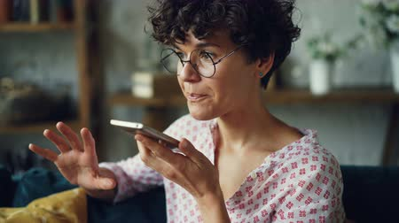 gravador : Smiling young woman is dialing telephone number then talking in loudspeaker mode holding smartphone in hand. Modern technology and communication concept. Stock Footage
