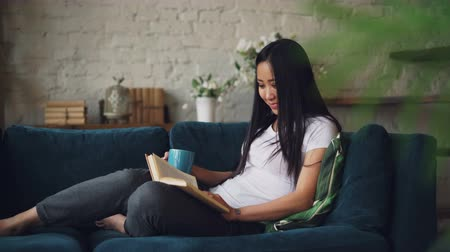 home life : Beautiful Asian woman is reading book enjoying funny story and laughing sitting on sofa in cozy loft style apartment and resting. Nice furniture and plants are visible.
