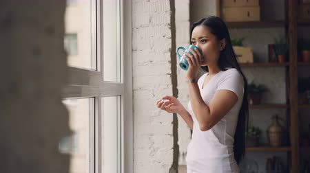 carelessness : Smiling Asian woman is drinking tea standing near the window and looking outside enjoying beautiful view and leisure time at home. Apartments, drinks and people concept.
