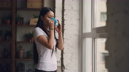 uzakta bakıyor : Relaxed Asian girl is going to the window with cup of coffee, looking outside and drinking then smiling and walking away. Apartment, beverage and youth concept. Stok Video