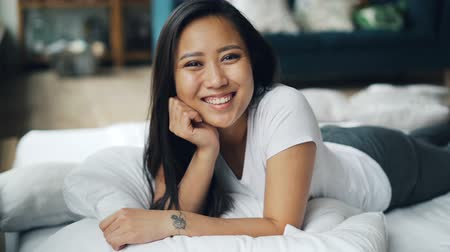 poduszka : Portrait of pretty Asian lady lying on bed at home, smiling then laughing and looking at camera. Relaxation, good mood, happiness and emotions concept.