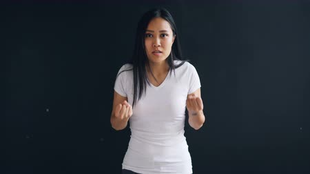 reakció : Portrait of furious Asian girl yelling and gesturing shaking fist expressing negative emotions against black background. Young people, problem and anger concept.