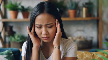 migrén : Good-looking Asian woman is suffering from headache frowning and touching her head massaging temples sitting indoors at home. Pain, people and health concept.