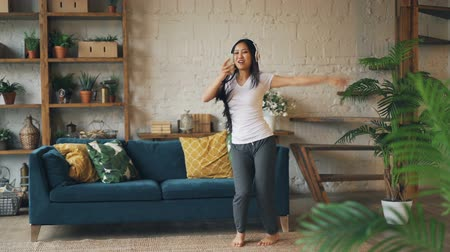 enjoyable : Slow motion of good-looking Asian woman dancing at home alone listening to music in smartphone through headphones and singing having fun. Technology and apartment concept.