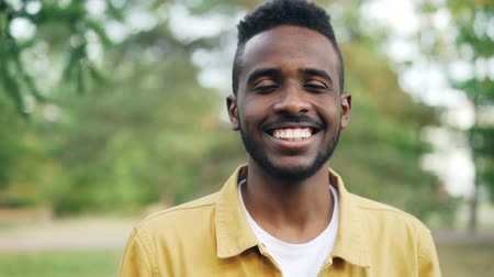 férfias : Slow motion portrait of carefree African American guy in trendy clothing standing in the park alone smiling and looking at camera. People and emotions concept.