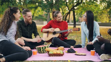 enjoyable : Charming young woman is playing the guitar sitting on blanket with friends on picnic, girls and guys are clapping hands and listening to music. Fun and nature concept. Stock Footage