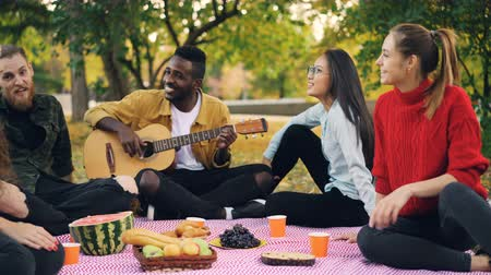enjoyable : Joyful African American guy is playing the guitar while his friends are singing sitting around him on picnic in park on autumn day. Musical instruments and people concept. Stock Footage