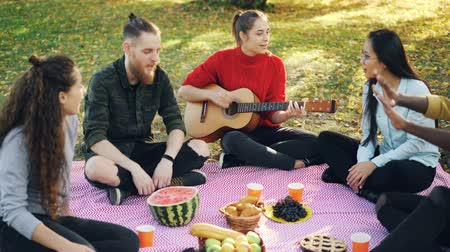 аплодисменты : Zoom-in of attractive girl playing the guitar on picnic while her friends are listening to music and singing then clapping hands. Outdoor activities and friendship concept. Стоковые видеозаписи