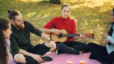 friendship dance : Creative young lady is playing the guitar while her male and female friends are singing and dancing sitting on plaid on meadow in park on picnic. Stock Footage