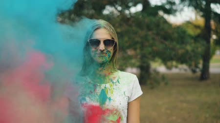 gençlik kültürü : Slow motion portrait of pretty young woman in sunglasses standing alone at Holi festival while colorful paint powder is thrown at her. Fun and youth concept.
