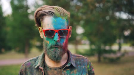 gençlik kültürü : Portrait of good-looking man standing in park at Holi festival with straight face covered with colorful powder and looking at camera wearing sunglasses.