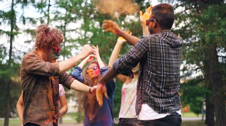recreational park : Excited girls and guys are dancing at Holi festival and throwing bright paint then laughing having fun outdoors. Holidays, millennials and nature concept.