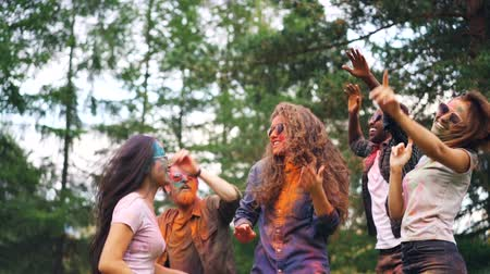 gençlik kültürü : Carefree students are dancing at party tossing hair having great time, their faces, hair and clothing are dirty with paint. Holi celebration, youth and nature concept.