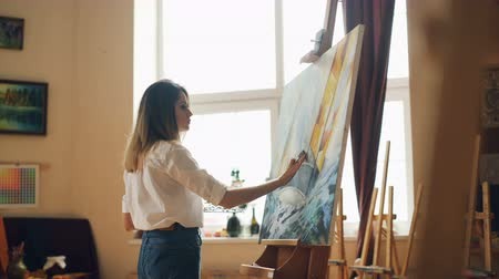 akrilik : Busy young woman is casual clothing is painting with oil paints standing near easel and holding brush and palette. Hobby, art and creative people concept. Stok Video