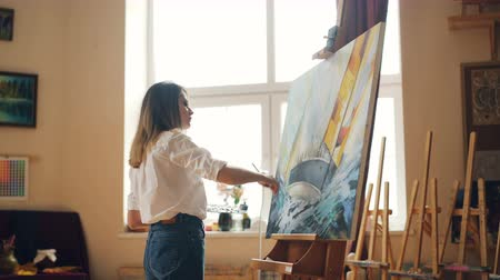 şaheser : Pretty girl painter is mixing paints on palette then painting seascape on canvas creating beautiful picture. Nice modern studio with tools is visible. Stok Video