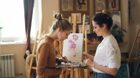 tavsiye : Pretty woman painting teacher is teaching young girl to mix paints on palette creating beautiful color during art class in nice modern studio. People and education concept. Stok Video