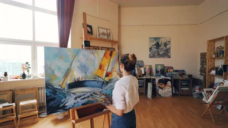 güzel sanatlar : Pan shot of female painter depicting marine landscape on canvas using oil paints, brush and palette working in workshop alone. Visual arts and youth concept. Stok Video
