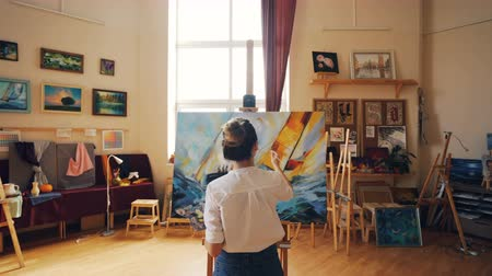 güzel sanatlar : Pan shot of young woman focused on painting seascape on canvas in nice light studio standing near easel alone and working. Fine arts and people concept. Stok Video