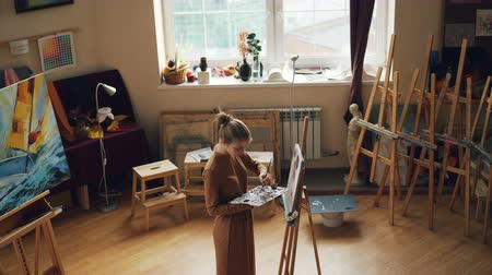 произведение искусства : High angle view of female painter working in workroom alone painting with brush and colors on palette. Wooden easels, artworks and tools are visible. Стоковые видеозаписи