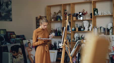 концентрированный : Pretty girl painter is working in workroom alone holding palette and brush and looking at canvas. Occupation, creative youth and workspace concept.