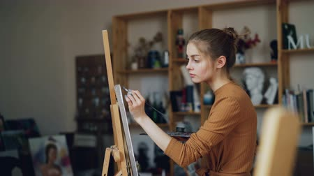 концентрированный : Beautiful blonde painter is painting picture in art studio alone using paintrush and palette with paints. Young woman is concentrated on creative work. Стоковые видеозаписи