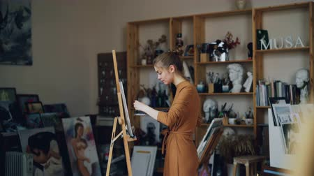 művésziesség : Art student is working in studio alone painting picture with oil paints using brush and palette standing in workroom near easel concentrated on work.