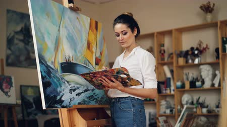 şaheser : Skillful female painter is working in studio alone painting picture on easel using oil paints, palette and brush enjoying her occupation. People and work concept. Stok Video