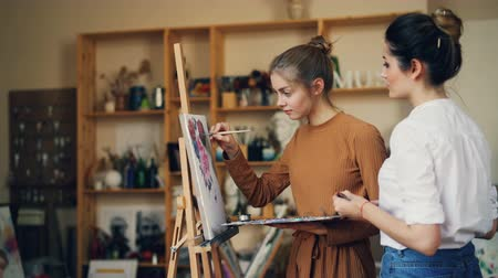 ručně malovaná : Talented student of art school is painting picture with her teacher working together in studio full of artworks and tools. Youth, creativity and people concept.