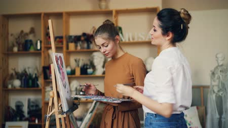 güzel sanatlar : Young women art teacher and student are painting together, talking and smiling during class in creative studio. Fine arts, education and people concept.
