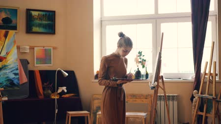 művésziesség : Cute young woman painter is working in studio holding palette and painting on canvas concentrated on creative work. Solitude, creativity and talent concept.