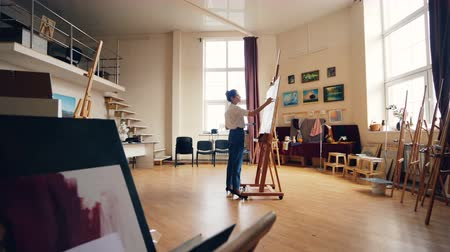 művésziesség : Slender woman is painting on canvas standing in center of light spacious studio alone creating masterpiece. Creative work, occupation and profession concept.
