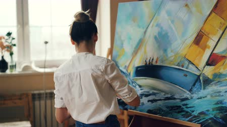 artistas : Professional female painter is working at picture using oil paints and palette-knife creating beautiful seascape on canvas. Painting technique and tools concept.