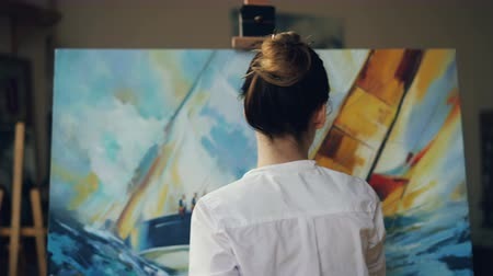 deha : Skilled artist pretty woman is painting seascape sea waves and boat with acrylic paints on canvas holding palette and brush creating masterpiece. People and arts concept. Stok Video