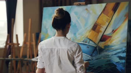 palette knife : Serious female artist is working at picture using oil paints and palette-knife creating beautiful marine landscape on canvas. Painting technique and painters concept. Stock Footage