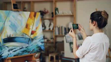művésziesség : Female painter is taking photo of her beautiful picture using modern smartphone camera touching screen standing in studio alone. Modern technology and arts concept.