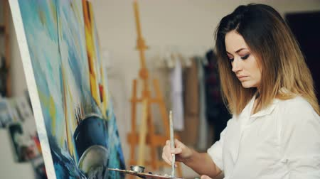 шедевр : Pretty young lady is busy painting picture in workshop using bright paint and stained palette. Girl is wearing casual clothing and is concentrated on her work. Стоковые видеозаписи